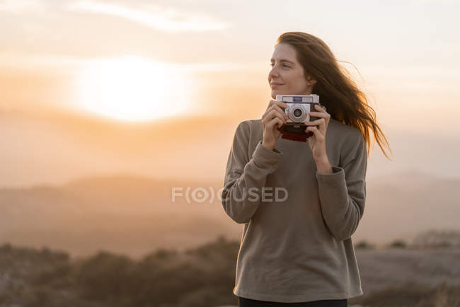 Spain, Barcelona, Natural Park of Sant Llorenc, woman with vintage camera at sunset — Stock Photo