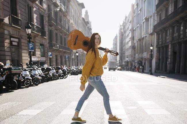Donna dai capelli rossi con una chitarra sulla traversata zebra — Foto stock