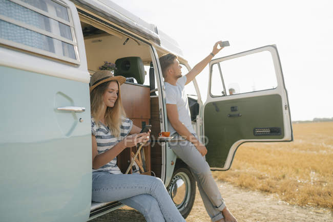 Young couple with cell phones relaxing at camper van in rural landscape — Stock Photo