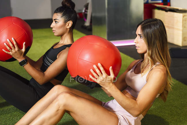 Young people doing ab training with fitness balls — Stock Photo