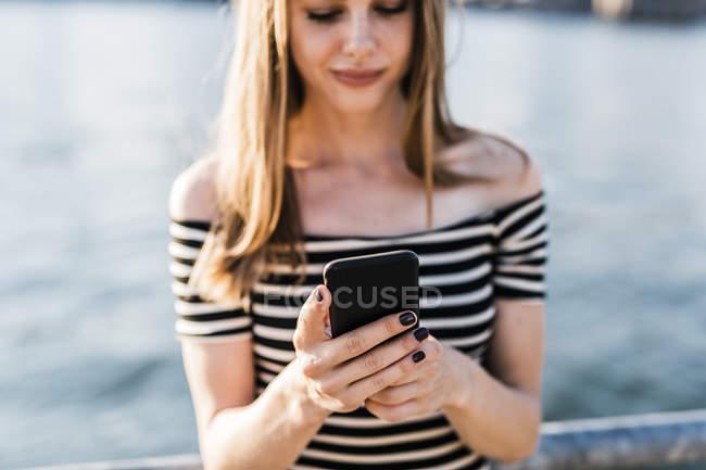 USA, New York, Brooklyn, woman using smartphone — Stock Photo