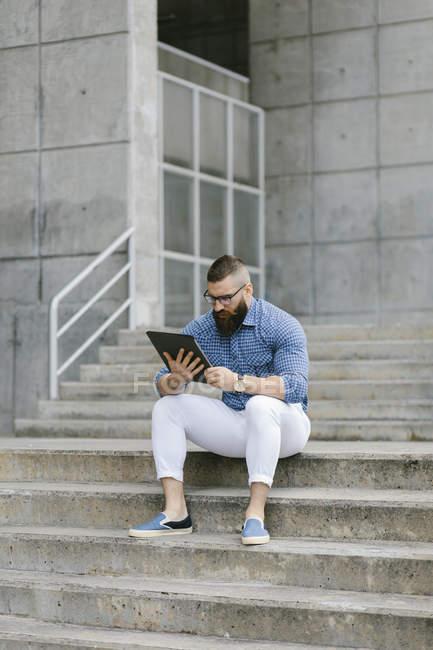 Бородатый хипстер-бизнесмен сидит на лестнице и использует цифровой планшет — стоковое фото