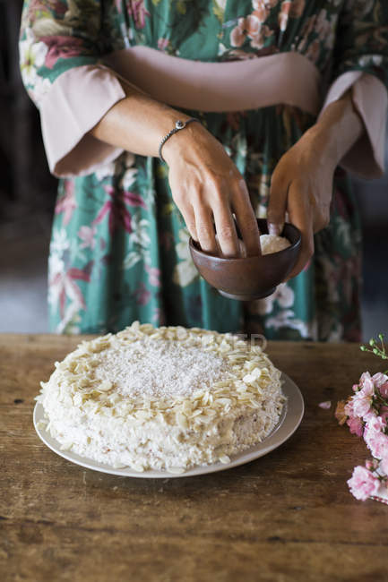Young woman garnishing home-baked cake, partial view — Stock Photo