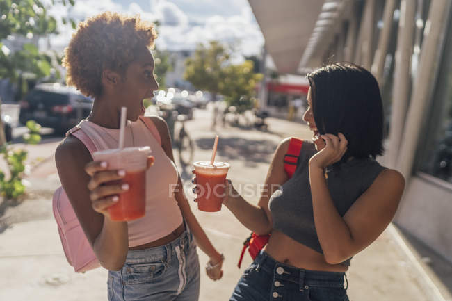 USA, Florida, Miami Beach, two carefree female friends having a soft drink in the city — Stock Photo