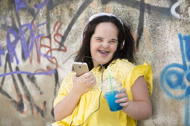 Adolescente com síndrome para baixo usando smartphone, segurando copo de plástico — Fotografia de Stock