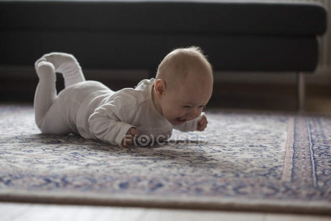 Screaming baby girl lying on carpet — Stock Photo