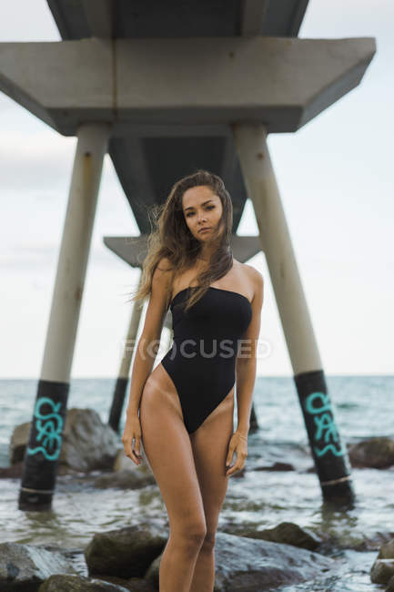Portrait of beautiful young woman wearing swimsuit and standing at the seafront — Stock Photo