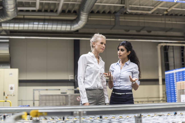 Two women discussing at conveyor belt in factory — Stock Photo