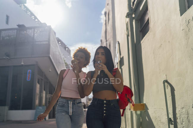 USA, Florida, Miami Beach, two female friends eating ice cream cones in the city — Stock Photo