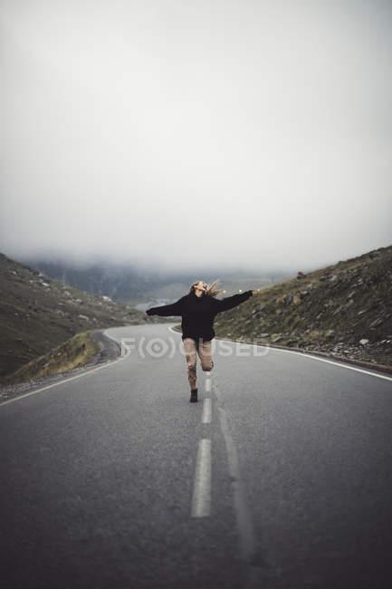 Блондинка бежит по дороге с горами на заднем плане — стоковое фото