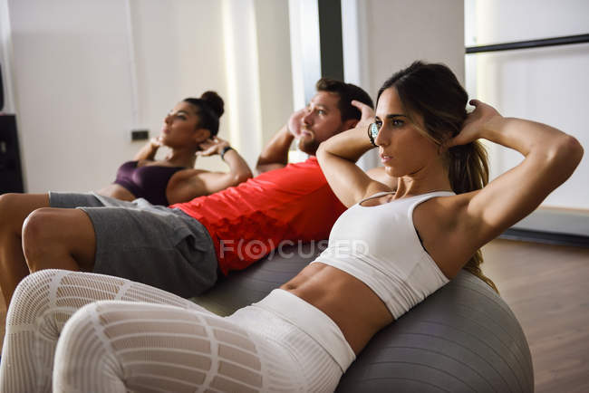 Young people doing crunches on a gym ball — Stock Photo