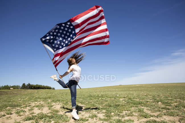 Happy girl holding American flag jumping on field in remote landscape — Stock Photo