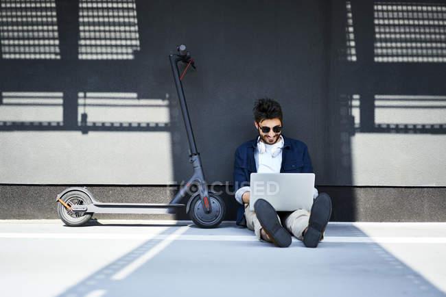 Hombre joven relajado sentado en el suelo, además de su scooter eléctrico utilizando el ordenador portátil - foto de stock