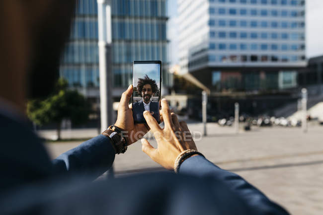 Spain, Barcelona, close-up of young businessman taking a selfie in the city — Stock Photo
