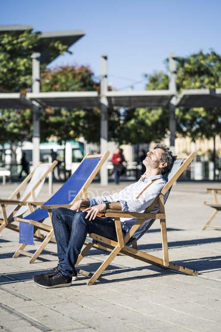 Homme mûr relaxant dans un transat sur une place de la ville — Photo de stock