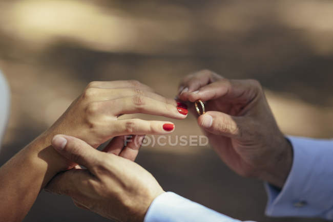 Bräutigam legt Ehering an Finger der Braut, Nahaufnahme — Stockfoto