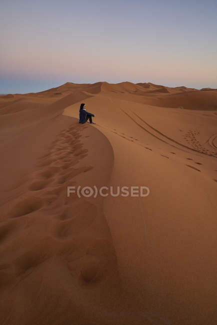 Morocco, woman sitting on desert dune at twilight — Stock Photo