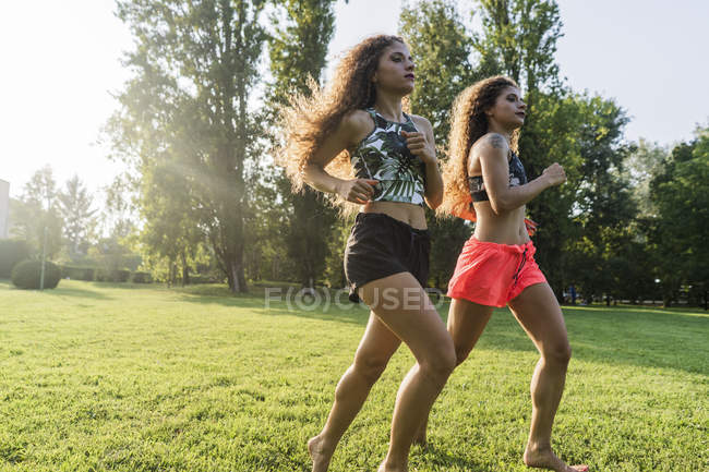Soeurs jumelles faisant jogging ensemble dans un stationnement au crépuscule de soirée — Photo de stock