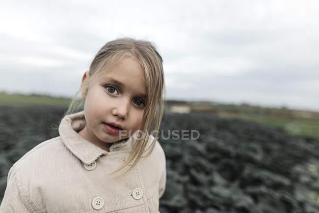 Retrato de uma menina em pé em um campo de repolho — Fotografia de Stock