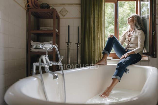 Mujer sentada en el alféizar de la ventana en el baño y mirando por la ventana - foto de stock