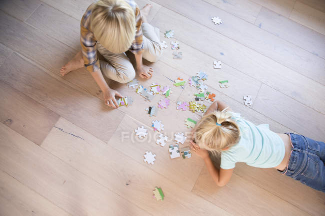 Брат и сестра лежат дома на полу, играют в пазззлы. — стоковое фото
