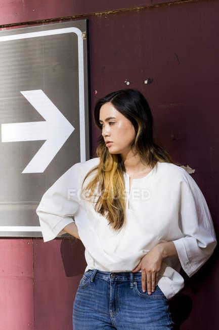 Mulher jovem esperando e olhando para o lado perto do sinal de seta — Fotografia de Stock