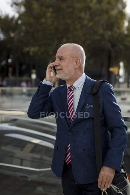 Senior businessman talking on cell phone in the city — Stock Photo