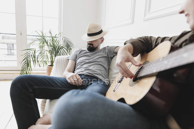 Relaxed couple sitting on couch, woman playing the guitar at home — Stock Photo