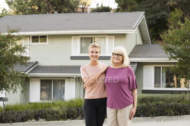 Портрет усміхненої жінки з мамою перед домом. — стокове фото