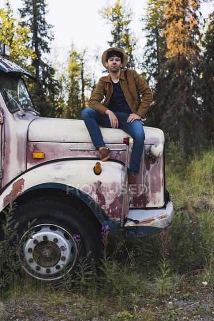 Крутий молодий чоловік, що сидить на розбитій вантажівці. — стокове фото
