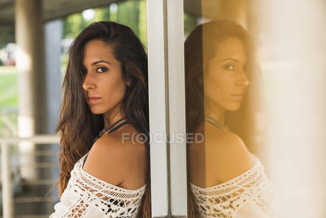 Retrato de mulher jovem inclinado contra uma janela — Fotografia de Stock