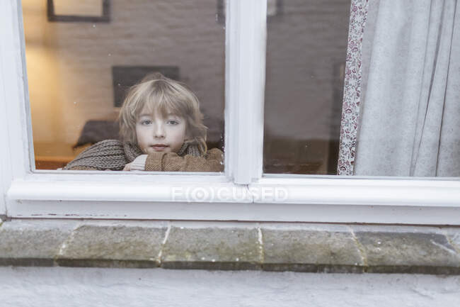 Portrait of pensive boy looking out of window — Stock Photo