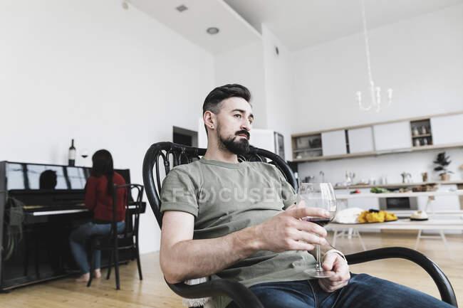 Coppia a casa, Uomo che beve vino, donna che suona pianoforte in sottofondo — Foto stock