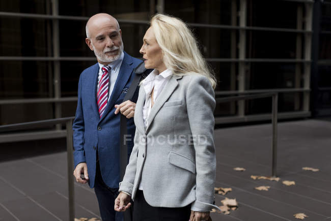 Senior businessman and businesswoman walking and talking in a foyer — Stock Photo