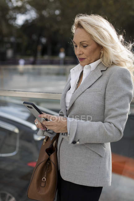 Senior businesswoman checking cell phone in the city — Stock Photo