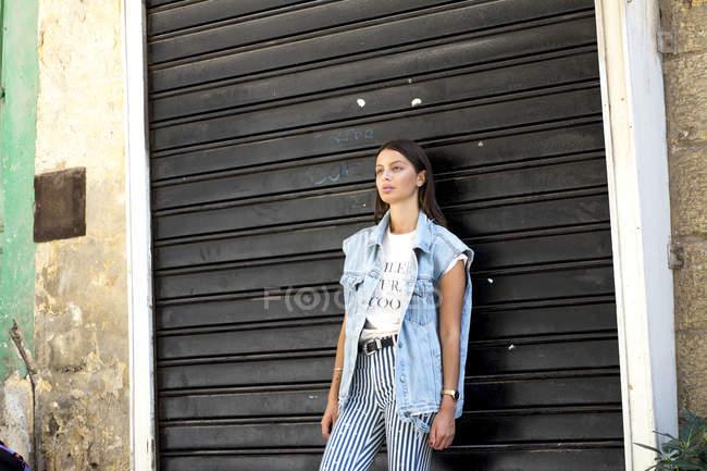Портрет модною молодої жінки, що стоїть перед роликовим затвор і дивлячись на відстані — стокове фото