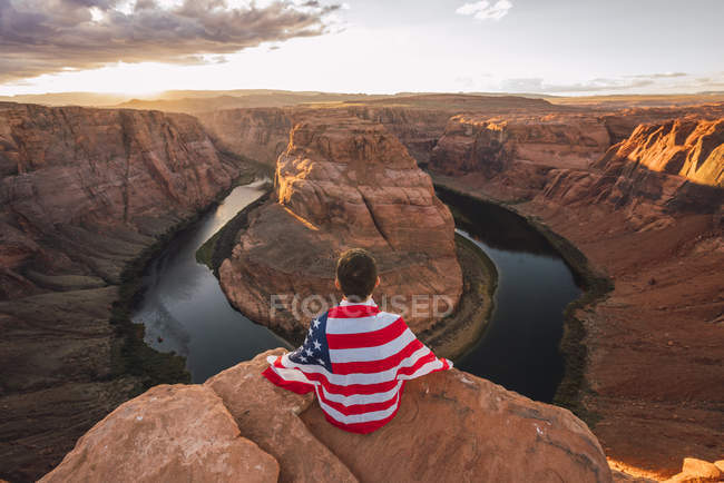 Usa, Arizona, Colorado River, Horseshoe Bend, joven sentado en el mirador con bandera americana. - foto de stock