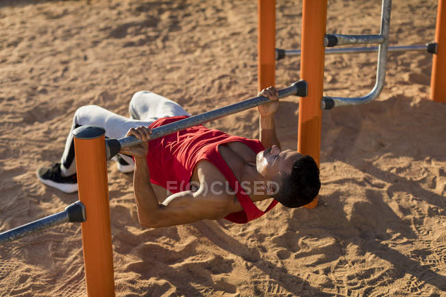 Fit man working out in climbing parcour, doing pull ups — Stock Photo