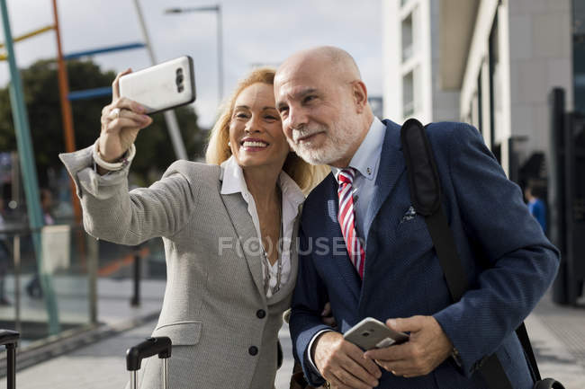 Senior businessman and businesswoman with baggage taking a selfie in the city — Stock Photo