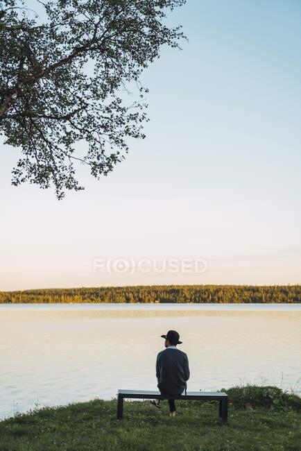 Молодой человек сидит на скамейке и смотрит на озеро — стоковое фото