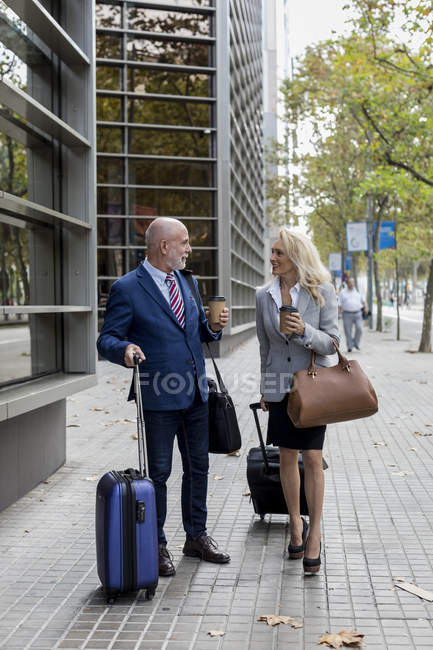 Senior businessman and businesswoman with baggage on the go in the city — Stock Photo