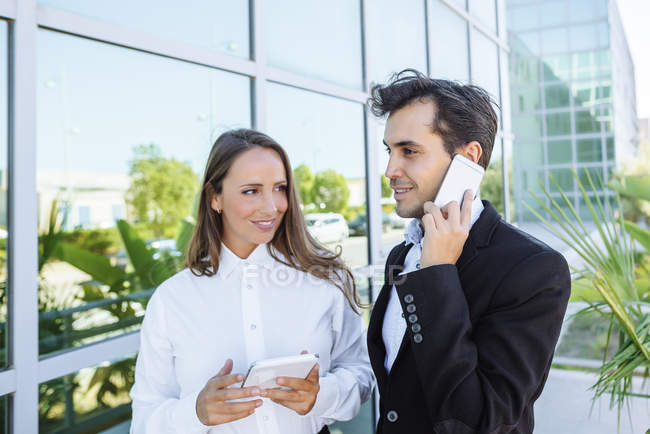 Smiling businesswoman and businessman with tablet and cell phone outside office building — Stock Photo