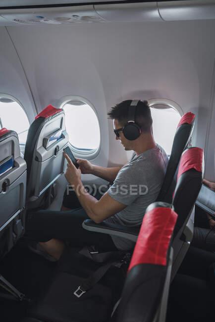 Man in airplane, using smartphone, headphones — Stock Photo