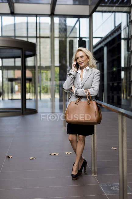 Senior businesswoman talking on cell phone in foyer — Stock Photo