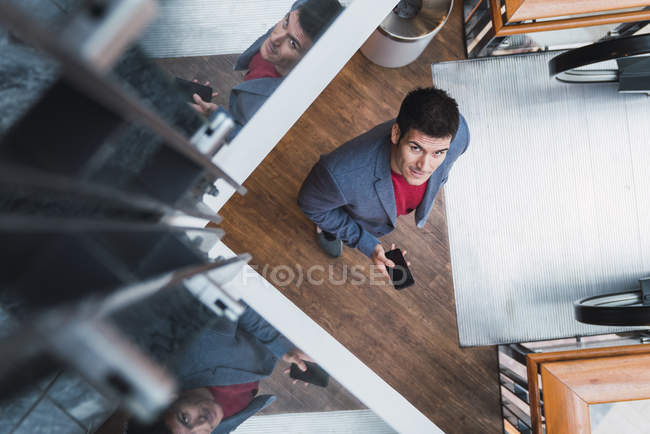 Businessman in lobby of a modern building, using smartphone — Stock Photo