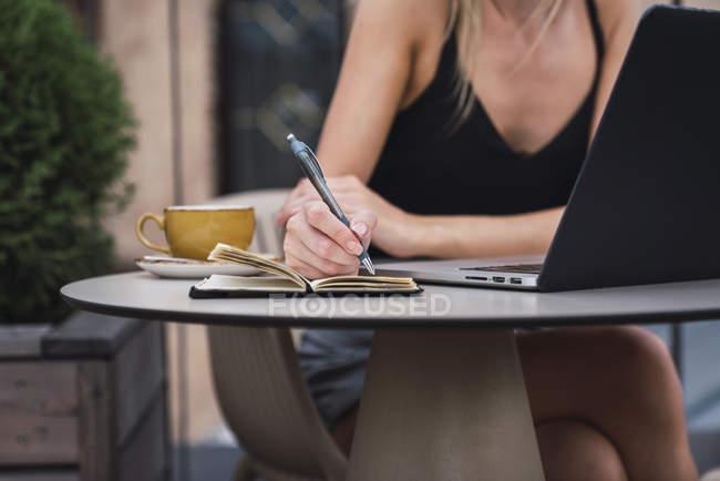 Молода жінка, сидячи на терасі на даху і беручи до нотаток, частковий вигляд — стокове фото