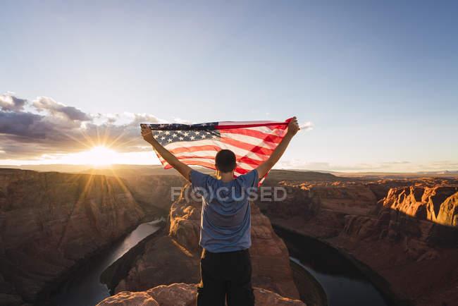Usa, Arizona, Colorado River, Horseshoe Bend, junger Mann auf einem Aussichtspunkt mit amerikanischer Flagge — Stockfoto