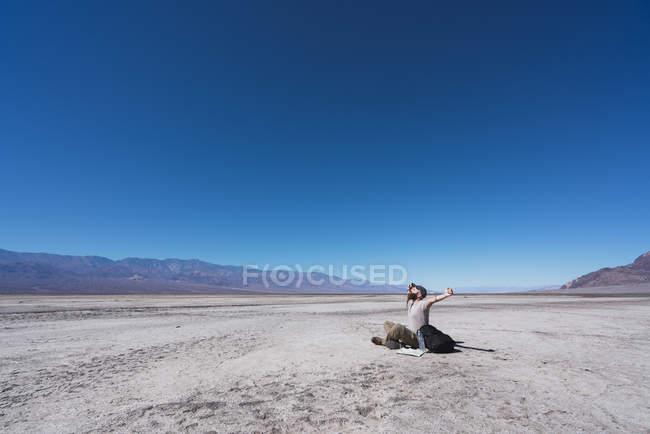 Usa, Californie, Death Valley, homme assis sur le sol dans le désert — Photo de stock