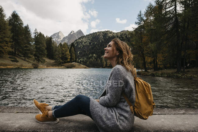 Switzerland, Grisons, Albula Pass, smiling woman on a hiking trip sitting at lakeside in mountainscape — Stock Photo