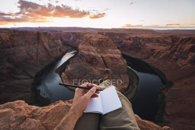 Estados Unidos, Arizona, Colorado River, Horseshoe Bend, joven en el punto de vista, notebook - foto de stock